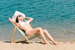 femme-mince-d-t-s-exposant-au-soleil-dans-le-deckchair-de-bikini-19572776